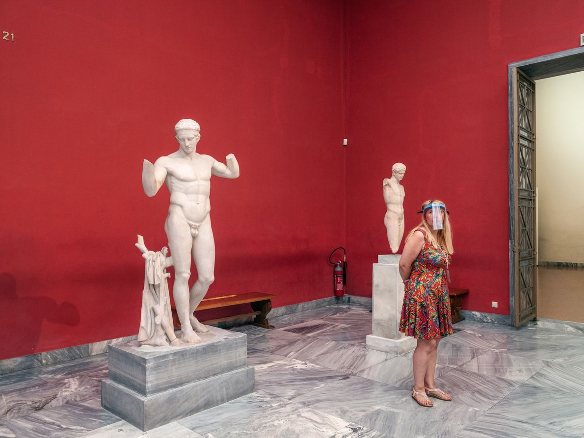 A museum guard at the National Archaeological Museum in Athens wears an obligatory face shield while ...
