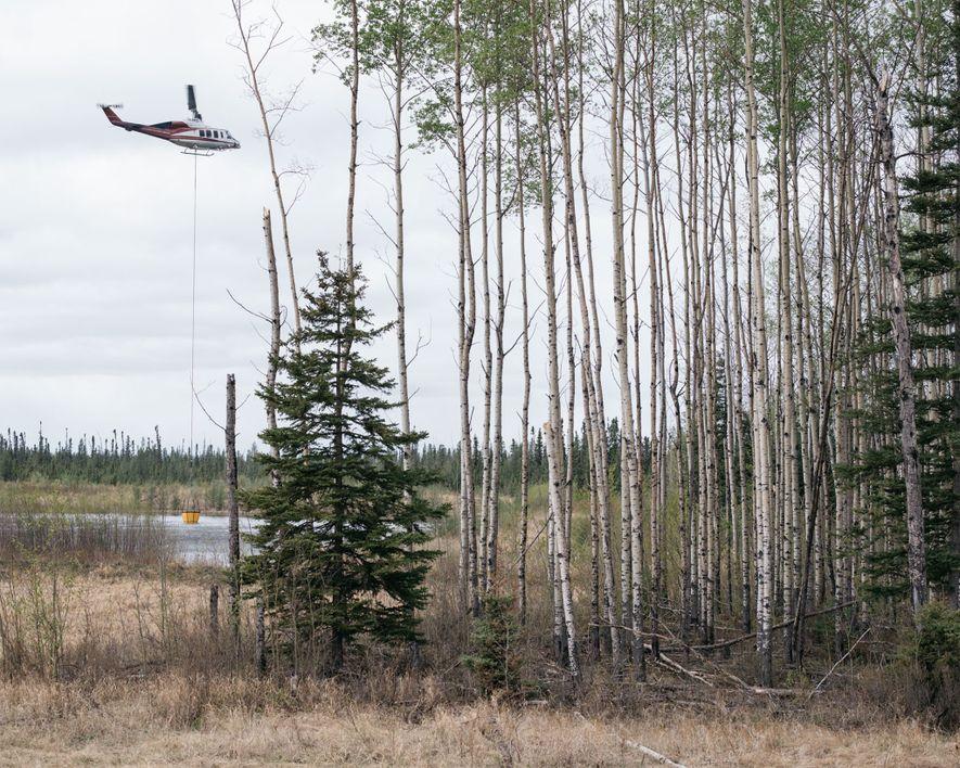 Un helicóptero recoge agua para apagar el incendio forestal en Fort McMurray, Alberta.
