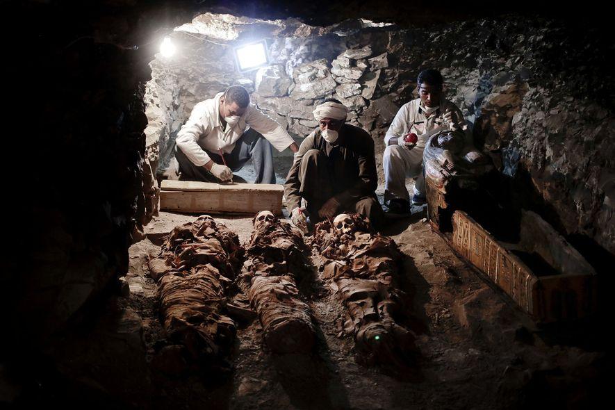 Arqueólogos trabajan con las momias descubiertas en la tumba del Imperio Nuevo que pertenecía a un ...