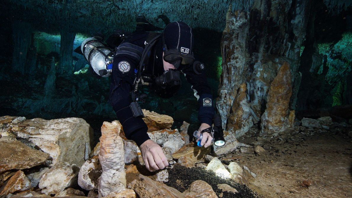 A diver collects charcoal from fires that once illuminated the cavern of La Mina as the ...