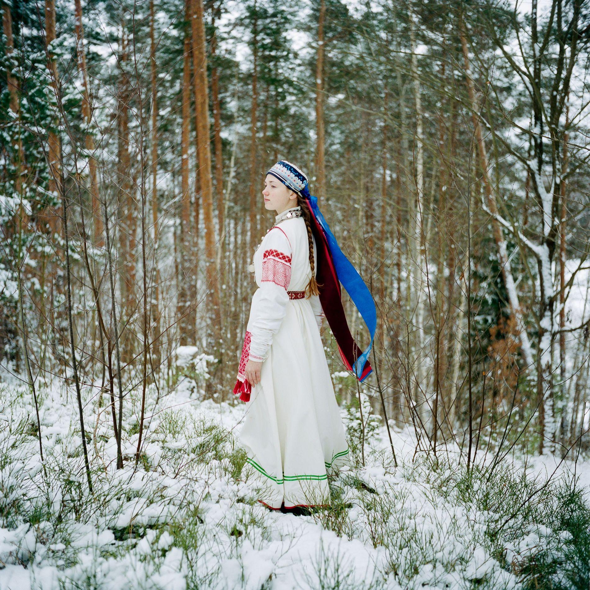 En Obinitsa, Estonia, una joven seto llamada Liisi Lõiv lleva puesto un traje tradicional en el jardín de sus abuelos. Las mujeres seto suelen tener trajes nuevos y viejos. Este es uno viejo, blanco, con mangas largas. La ropa también revela otros detalles. Una mujer casada se cubre el pelo, mientras que una mujer soltera o una joven como Liisi lleva solo una corona o pañuelo, dejando a la vista su larga trenza. Hoy en día, los setos solo llevan sus trajes tradicionales en ocasiones especiales. Liisi dice que bordó ella misma su traje. «Estoy orgullosa de ser seto», afirma. «Es de donde vengo, donde crecí».