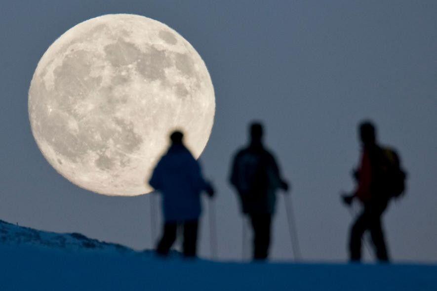 Unos senderistas contemplan la luna casi llena que se eleva tras la cima del Weissfluhjoch en ...