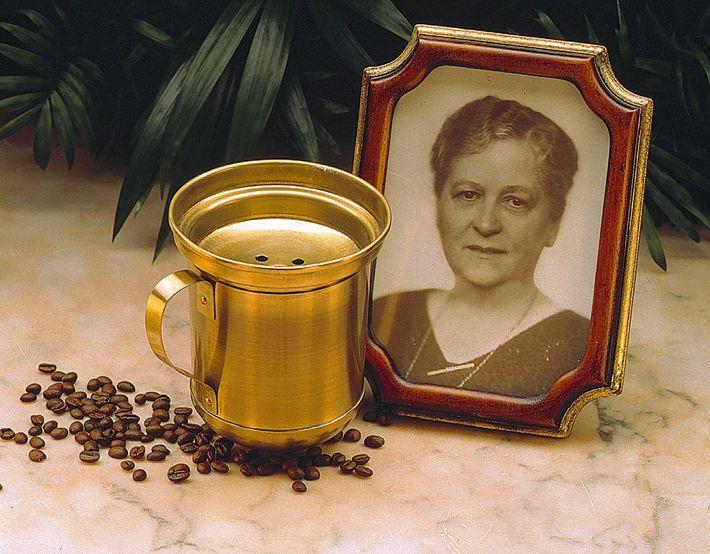 Una fotografía de Melitta Bentz junto a granos de café y una taza de latón.