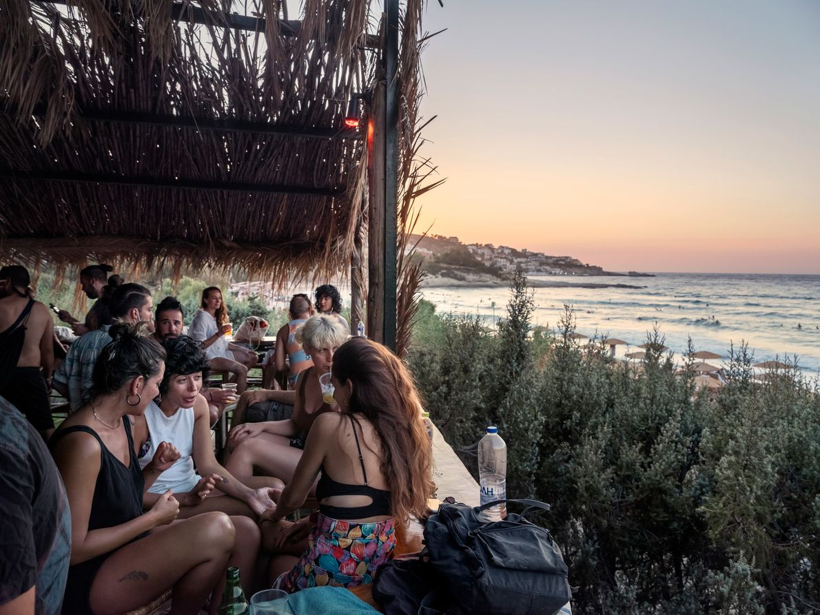 Friends gather at a beach bar at sunset on Mesakti Beach, on Ikaria. This year, the ...