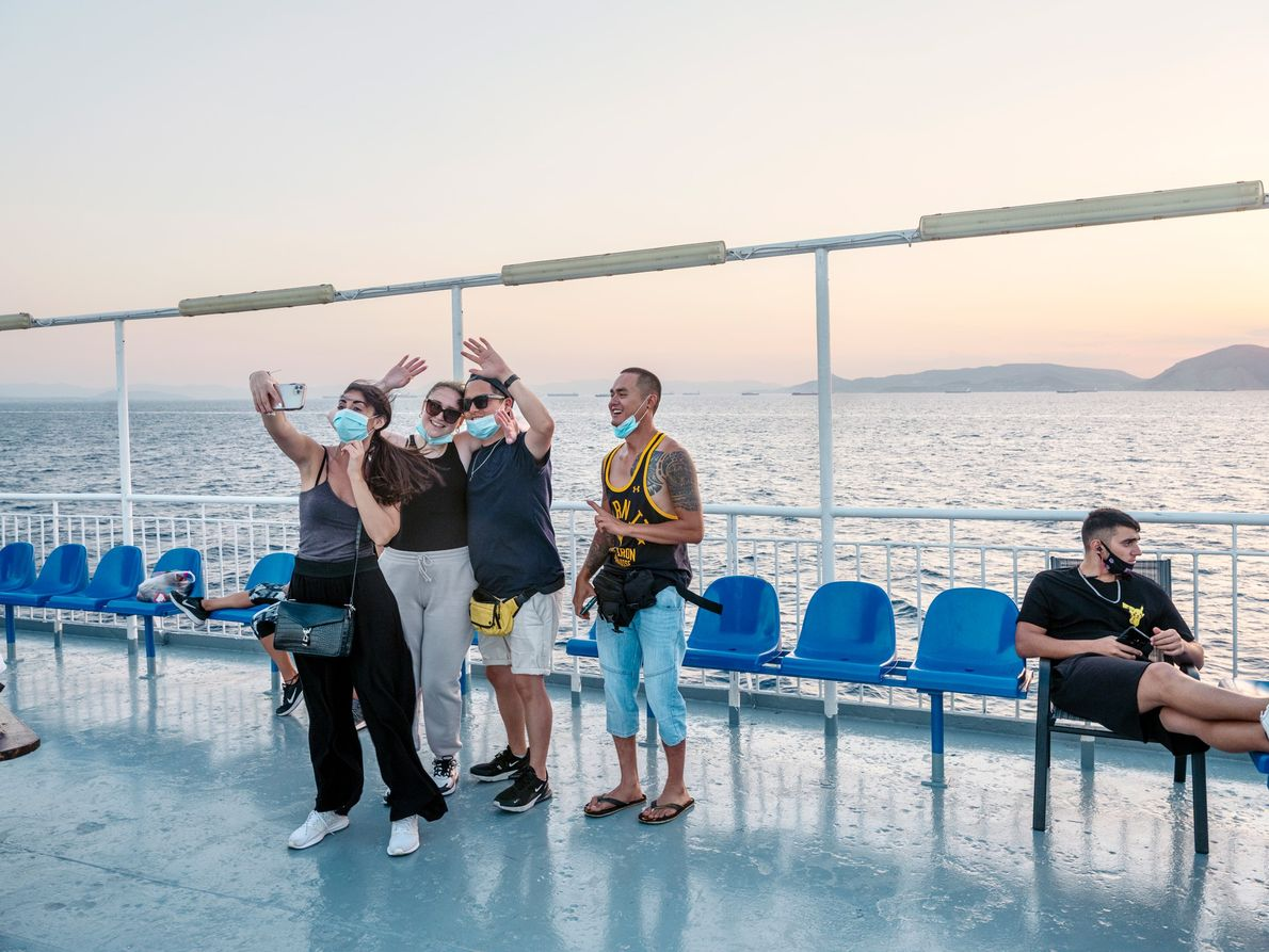 A group of friends takes selfies aboard a ferry bound for Santorini.