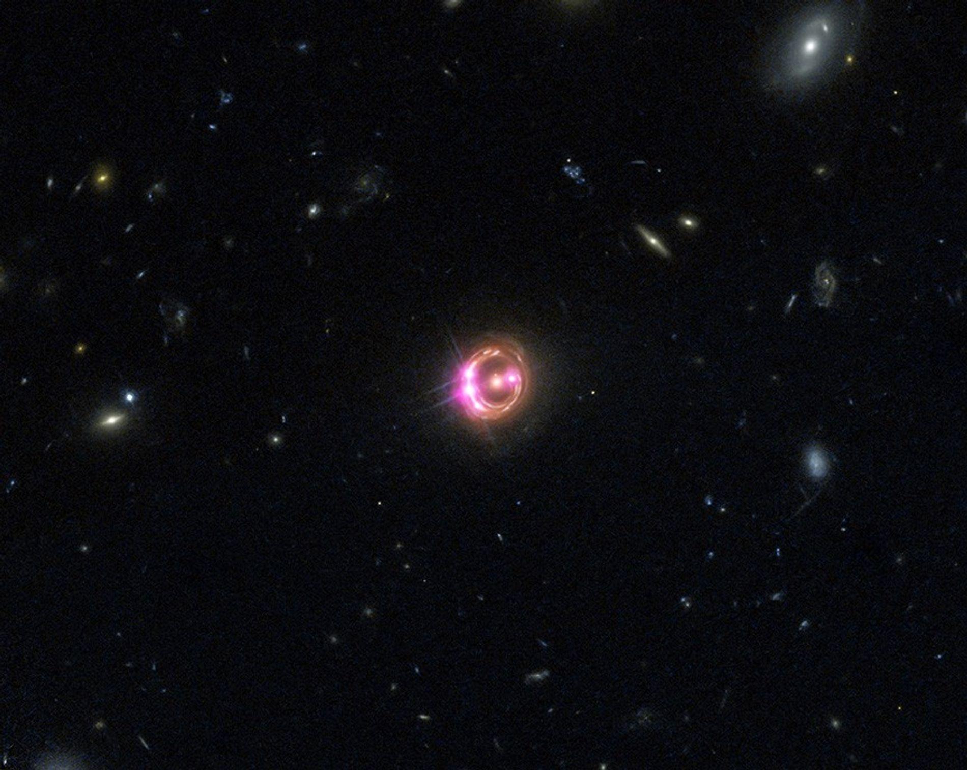 Varias imágenes de un cuásar distante se ven en esta imagen combinada del Observatorio Chandra de rayos X y el telescopio espacial Hubble de la NASA. Una gran galaxia en primer plano curva tanto la luz del cuásar que actúa como lente, provocando la aparente duplicación.