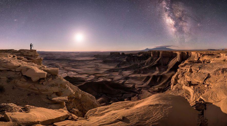 Un fotógrafo solitario en Moab, Utah. Su silueta se recorta en el firmamento que revela la ...