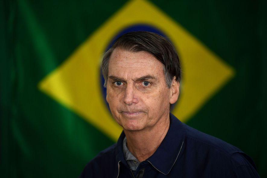 Bolsonaro, líder del Partido Social Liberal de derechas, ante la bandera brasileña el día de las ...