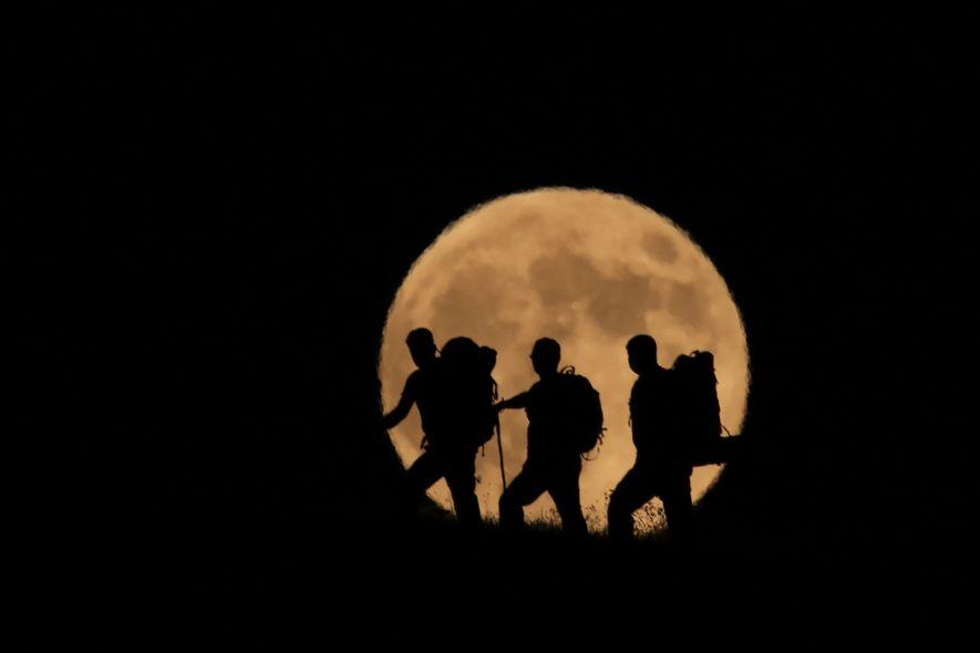 La luna llena se eleva tras las siluetas de unos senderistas en el monte Artos, en ...