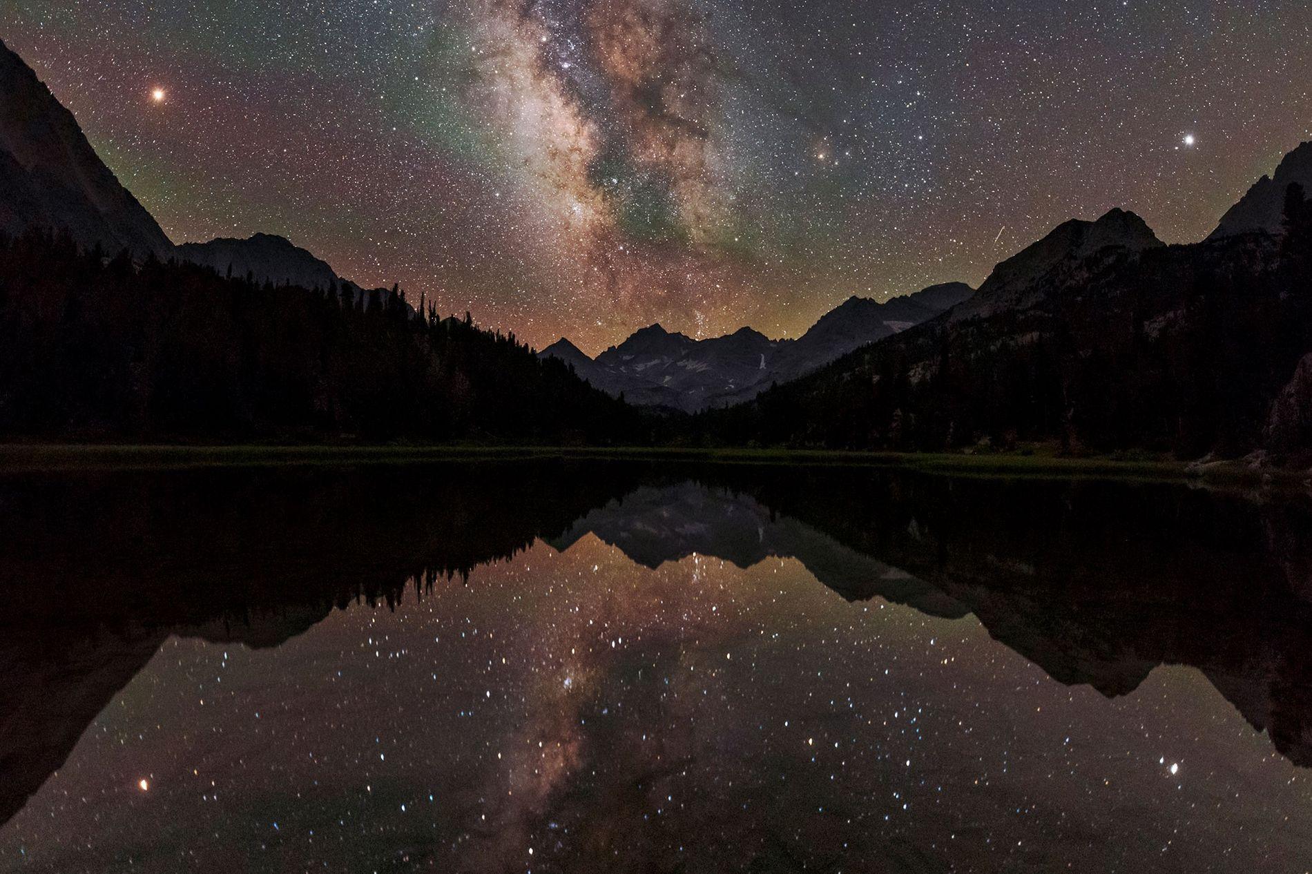 La Vía Láctea se refleja sobre un lago de montaña en California. Desde dentro de uno de los brazos espirales de la galaxia, podemos contemplar la densa región interna del disco en forma de una franja distintiva de estrellas, pero nos cuesta más percibir la forma a gran escala de la galaxia.
