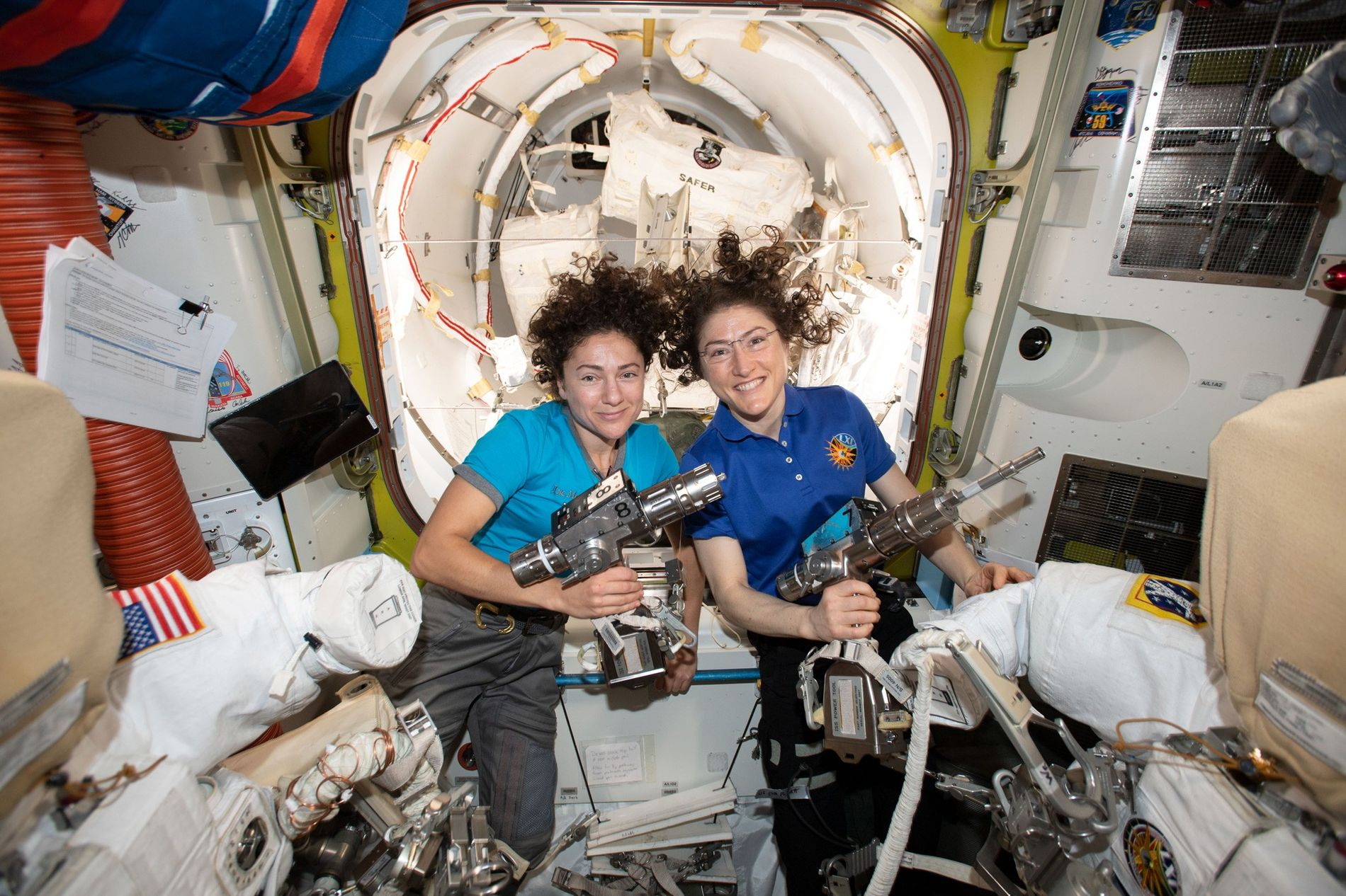 Las astronautas de la NASA Jessica Meir (izq.) y Christina Koch posan dentro de la esclusa Quest a bordo de la Estación Espacial Internacional mientras preparan los trajes espaciales y las herramientas que usarían en el histórico paseo espacial del 18 de octubre.