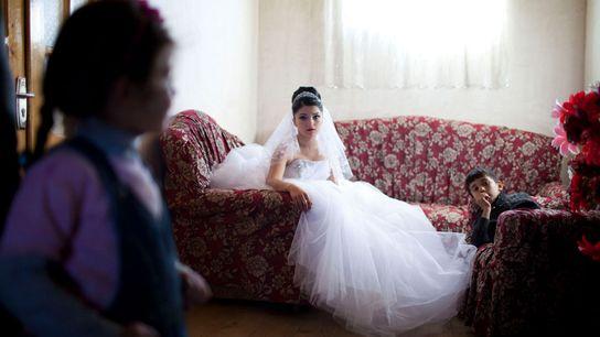 Imagen de una novia adolescente sobre un sillón de flores.