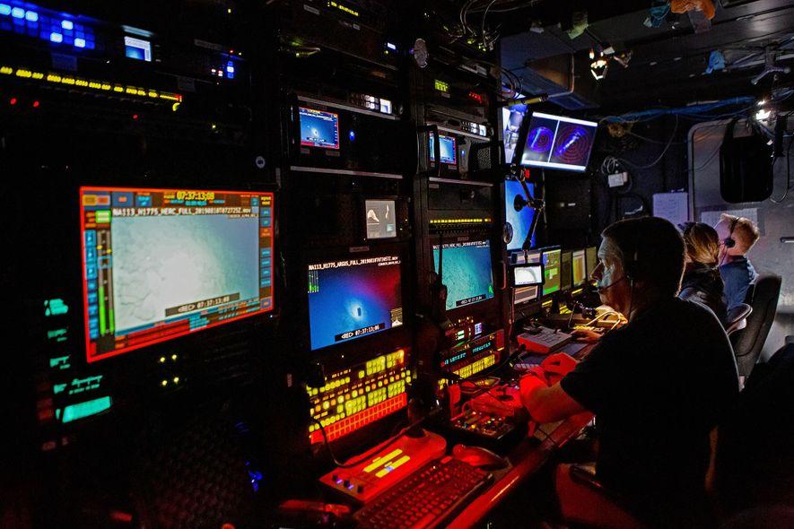 Dentro de la sala de control, los miembros de la tripulación pilotan vehículos remotos (ROV) y ...