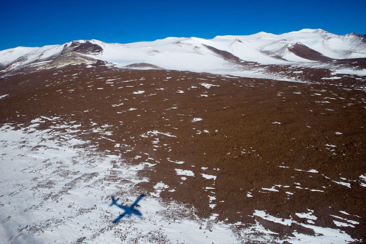 La sombra de un avión Twin Oter que vuela bajo sobre el pico Graphite. Debido a …