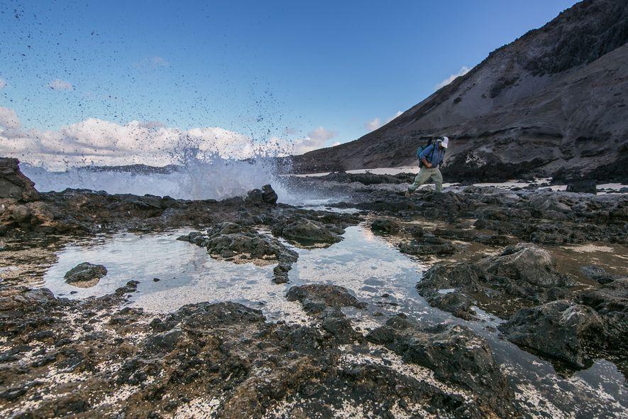 Un hombre que lleva una mochila casi es alcanzado por una ola.