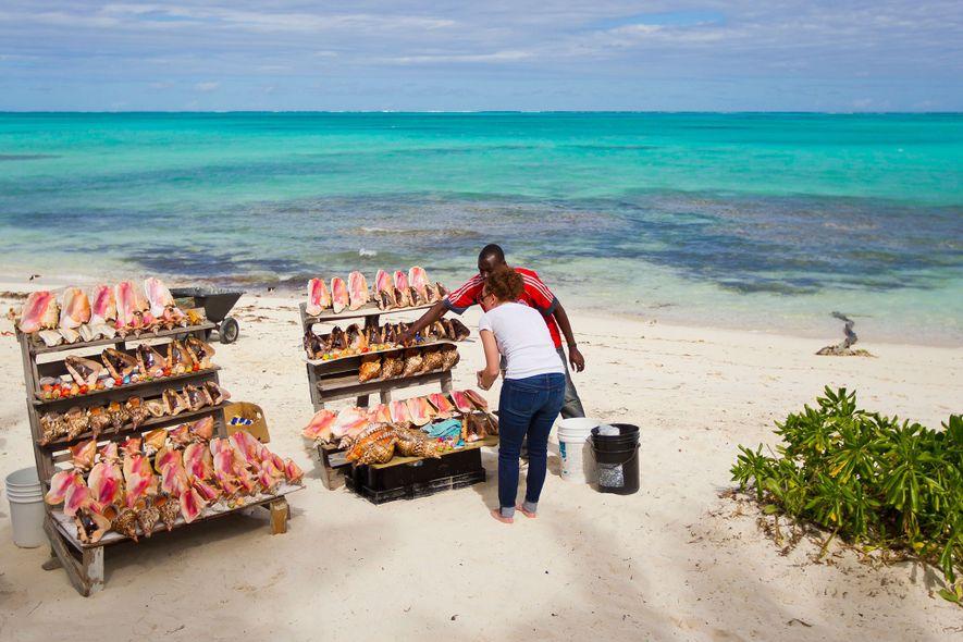 Una mujer compra conchas de caracol en un puesto de souvenirs junto a la playa en ...