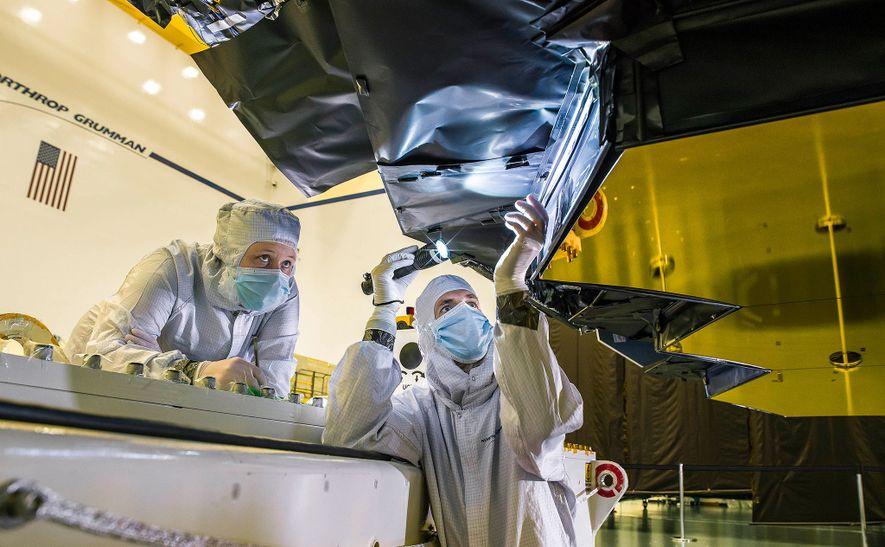 Ann Meyer, técnica de mantas térmicas de Northrop Grumman, y Larkin Carey, ingeniero óptico de Ball Aerospace, inspeccionan la barrera de protección del espejo principal del Webb.