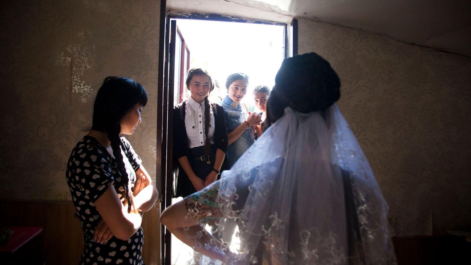 Imagen de unas niñas admirando el vestido de novia de su amiga
