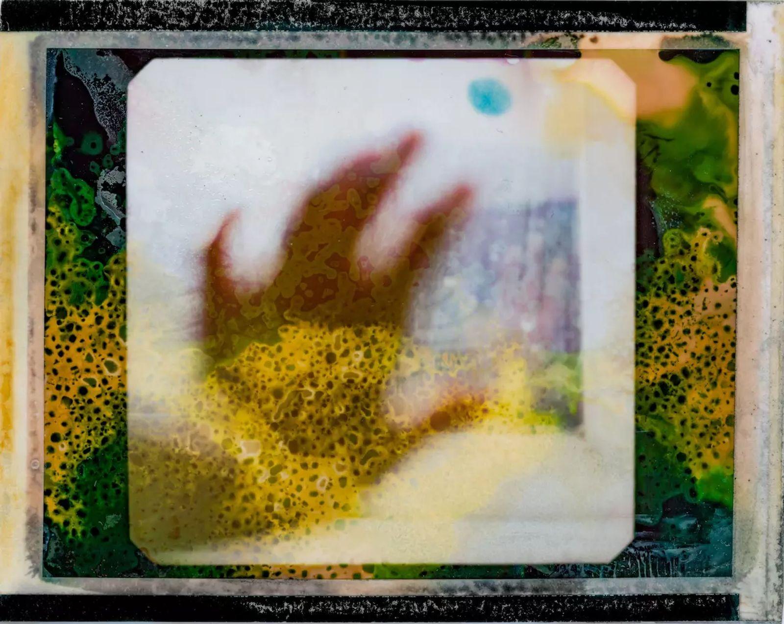 Fotografía de una mano extendida hacia la ventana