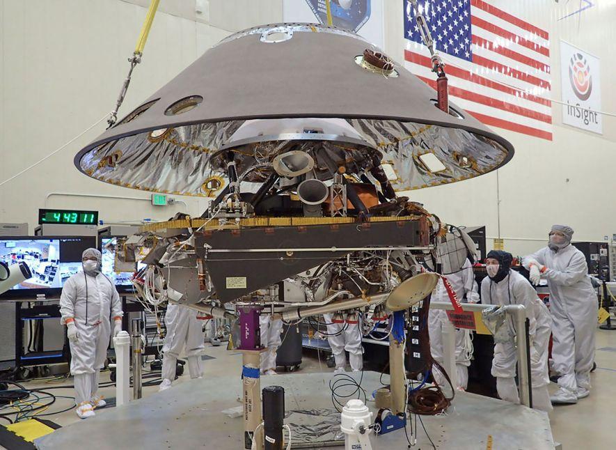 El escudo posterior de la nave InSight de la NASA se baja sobre el aterrizador de ...