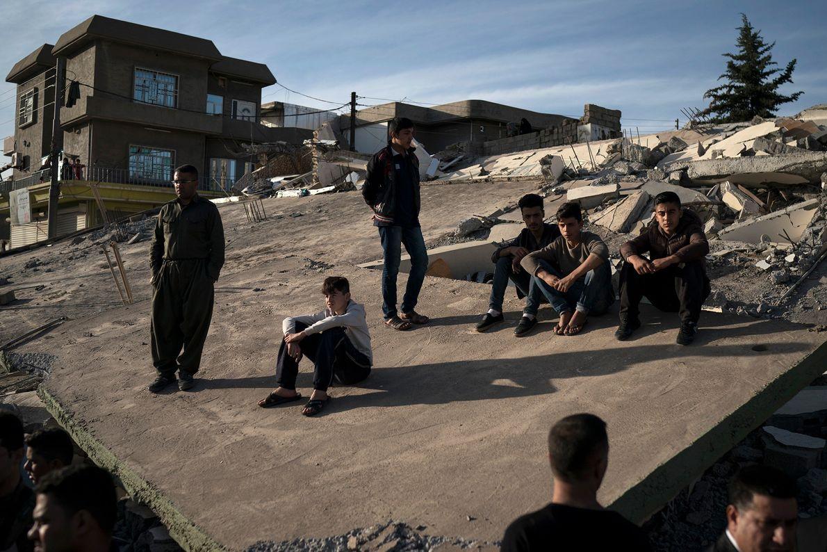 Chicos sentados en el tejado de una casa destruida