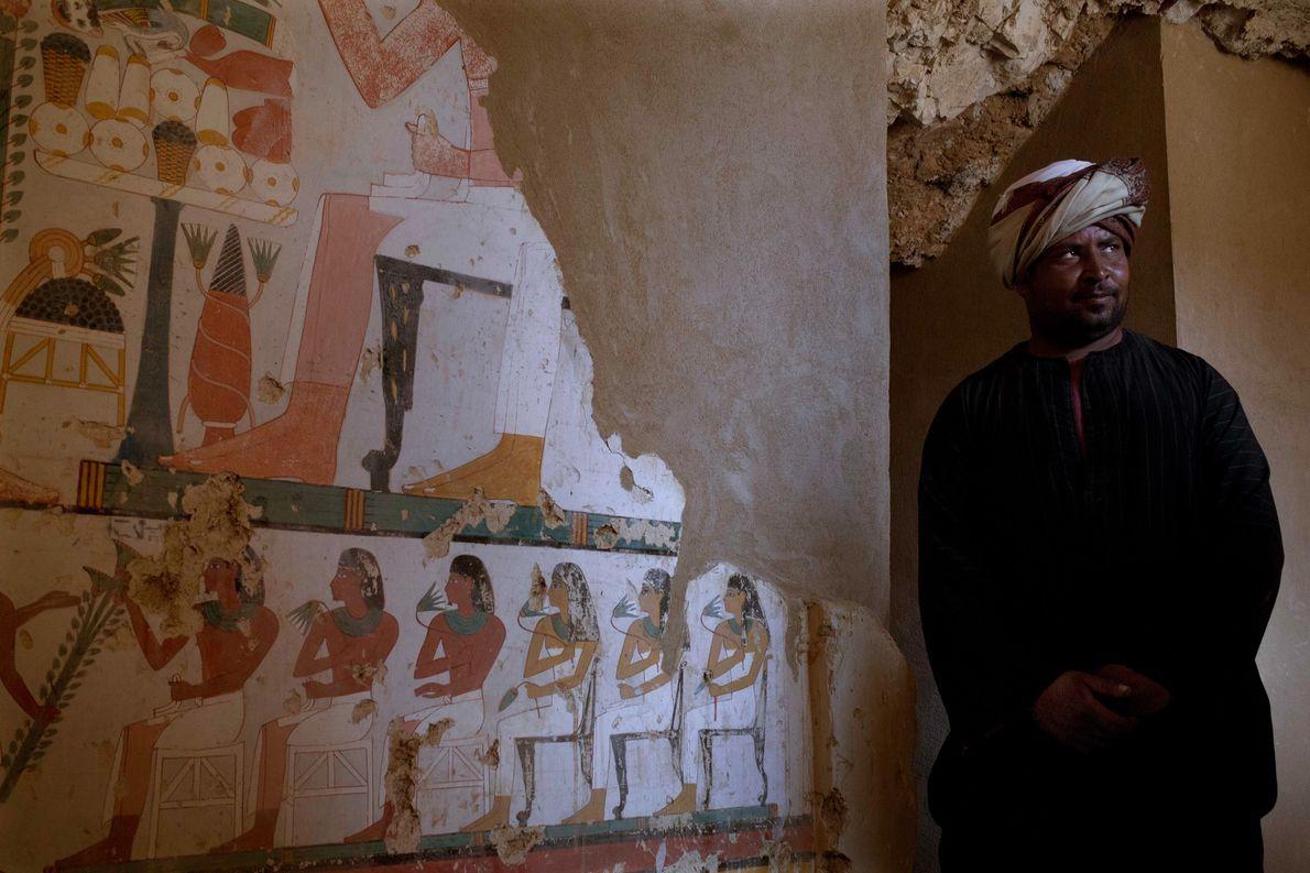 Un trabajador junto a un elaborado mural funerario en la pared de una tumba recién descubierta …
