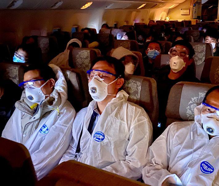 Pasajeros con equipo de protección en el vuelo