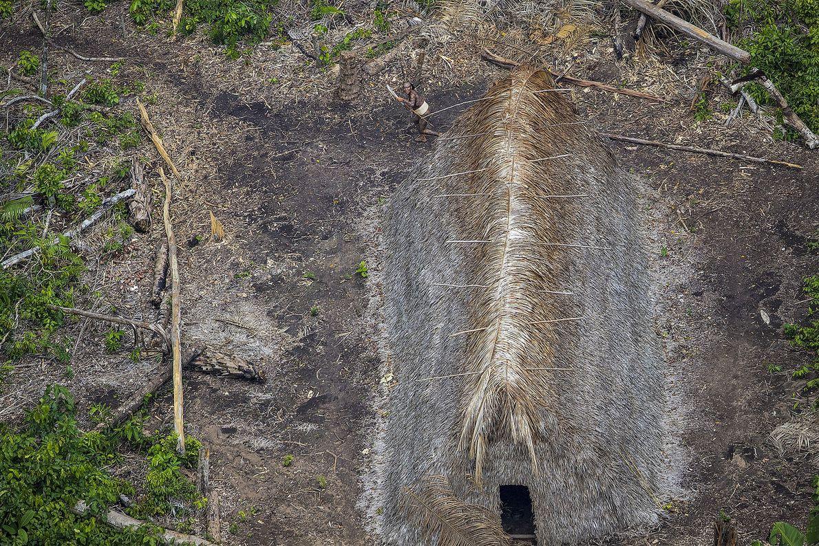 Imagen de una larga cabaña de tejado de paja en la selva amazónica vista desde arriba.