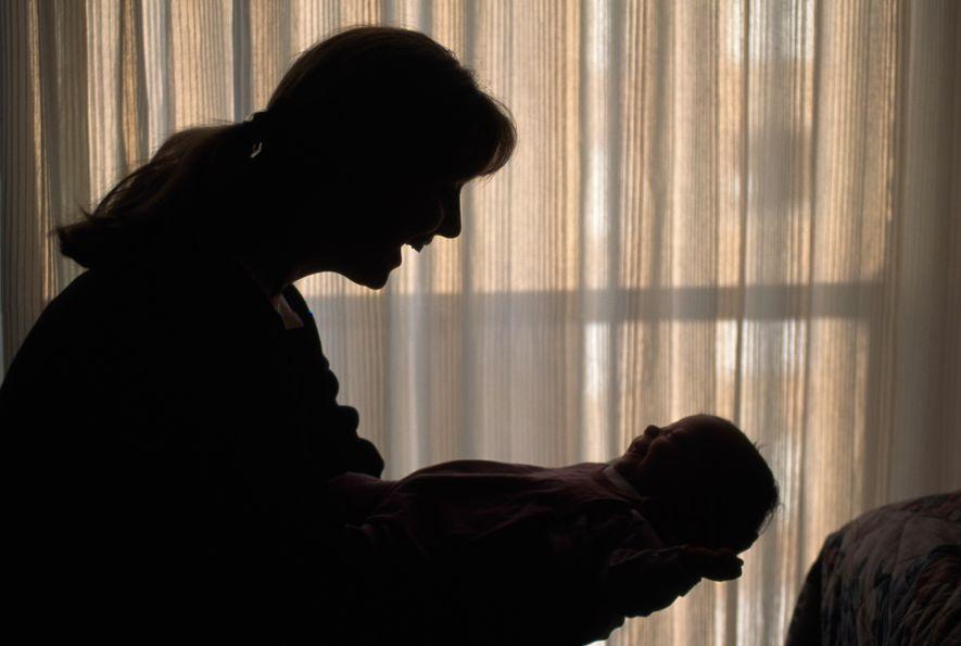 Una madre coge en brazos a su bebé.