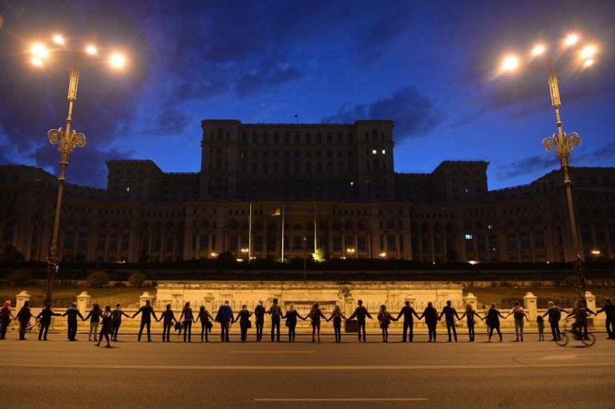 Los manifestantes forman una cadena humana alrededor del Parlamento rumano en Bucarest el 21 de septiembre ...