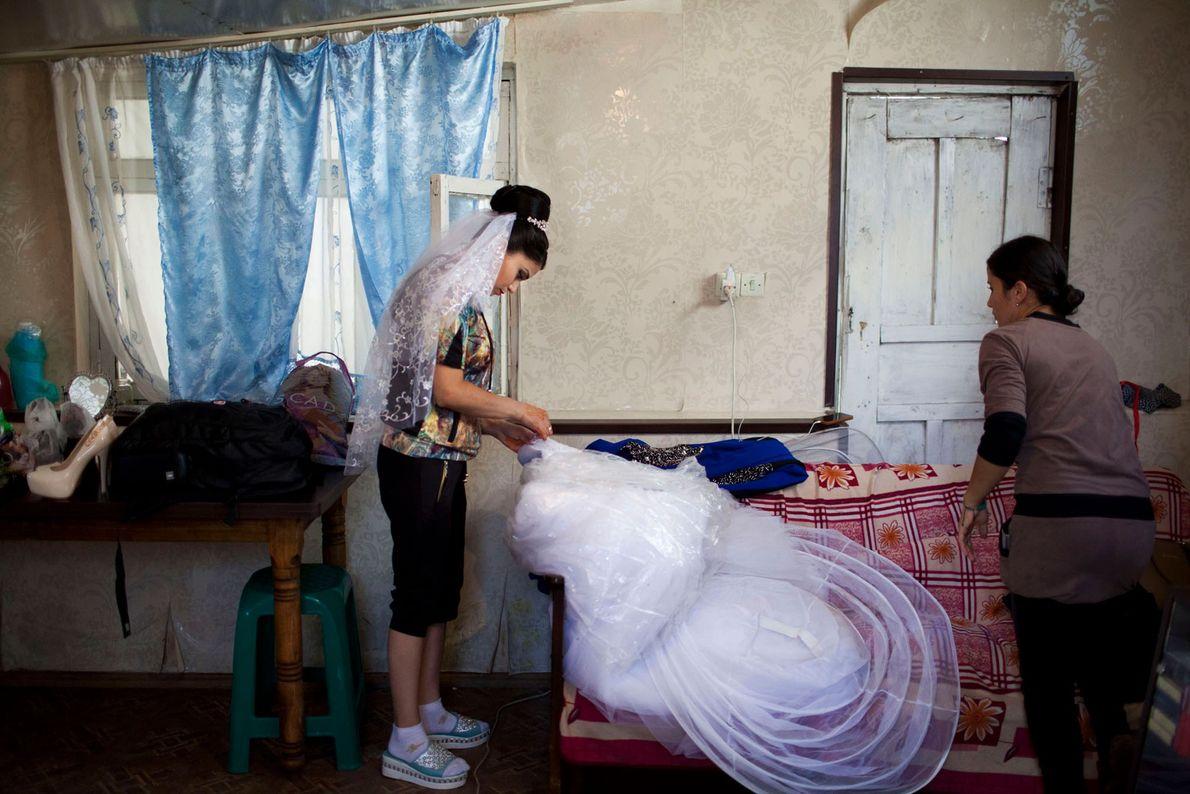 Imagen de una novia adolescente arreglando su vestido de novia