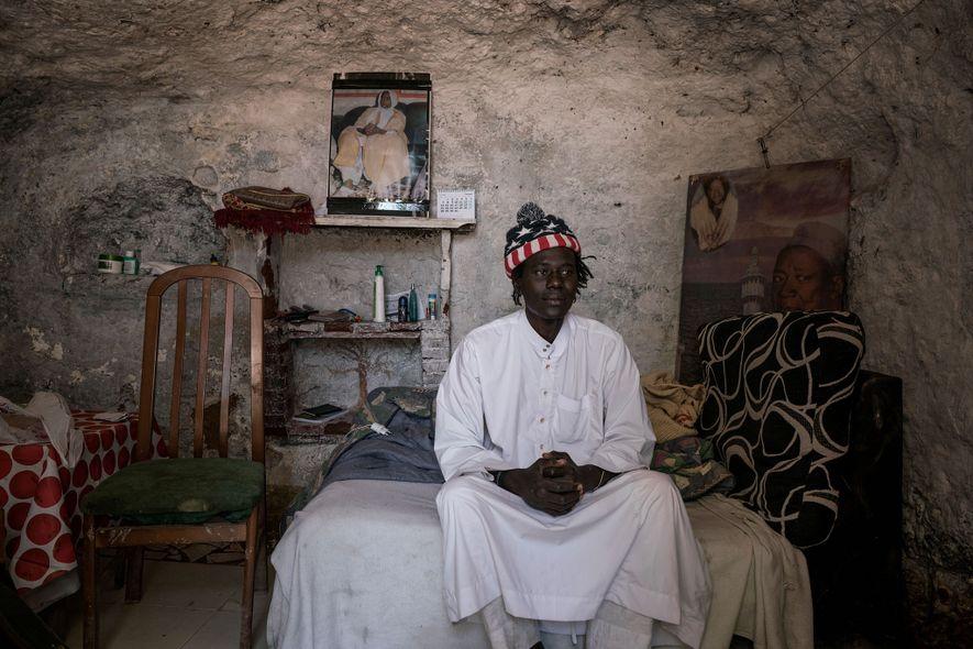 Mbacke sentado en su cama