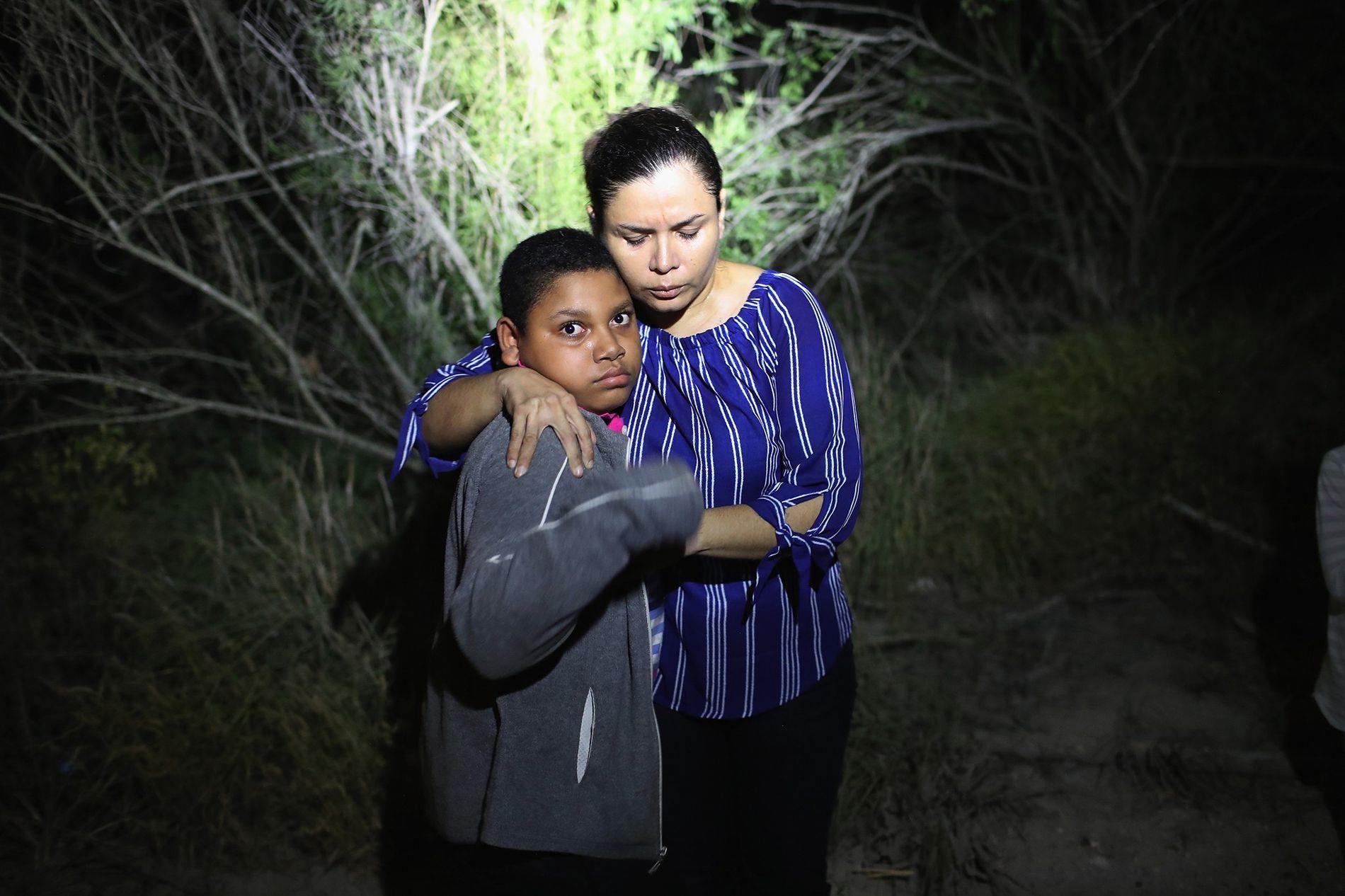 Un foco de la Patrulla Fronteriza de los Estados Unidos ilumina a una madre hondureña y su hijo cerca de la frontera entre México y Estados Unidos el 12 de junio de 2018 en McAllen, Texas.