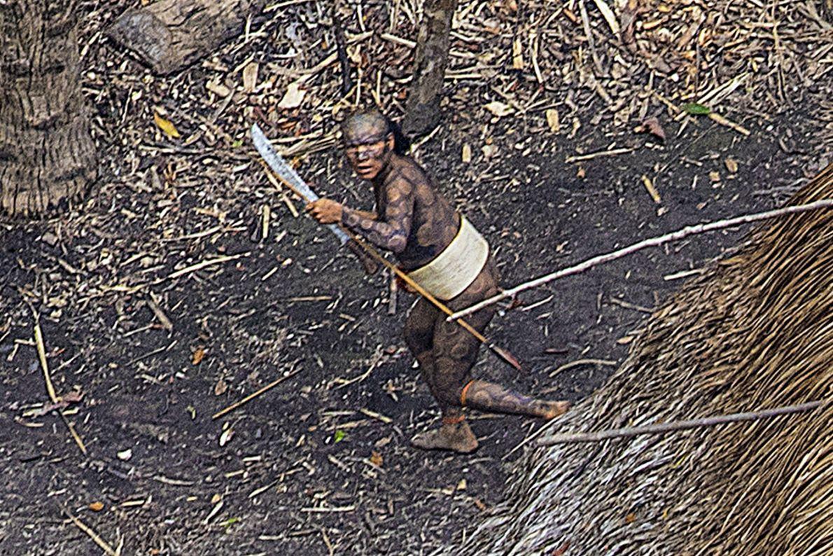Imagen de un indígena con pintura corporal, llevando un machete