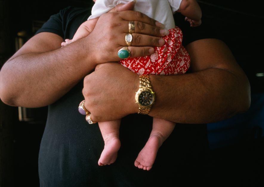 El músico Kurt Kipapa, padre de 10 hijos, coge en brazos a su hijo más pequeño.