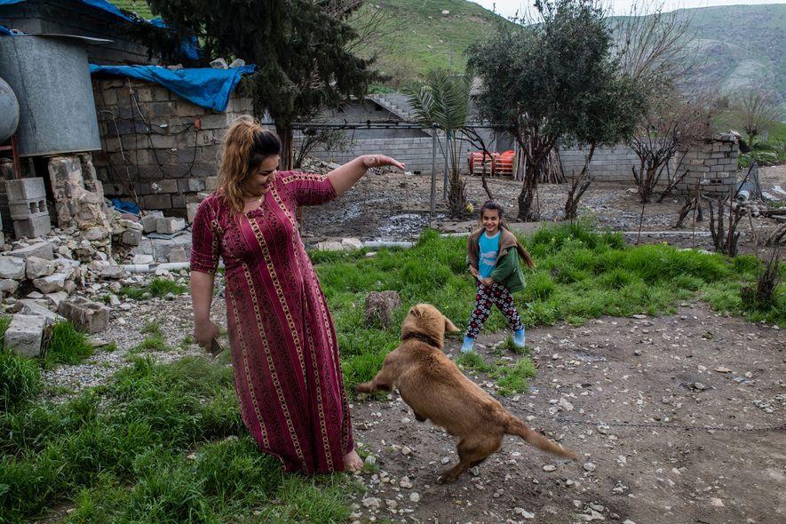 En el Kurdistán iraquí, una mujer juega con el perro de la familia en una aldea ...