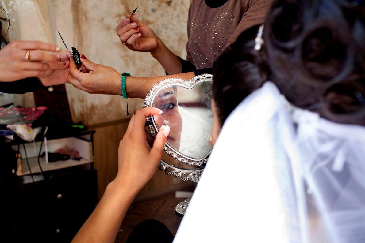 Imagen de una novia adolescente maquillándose el día de su boda