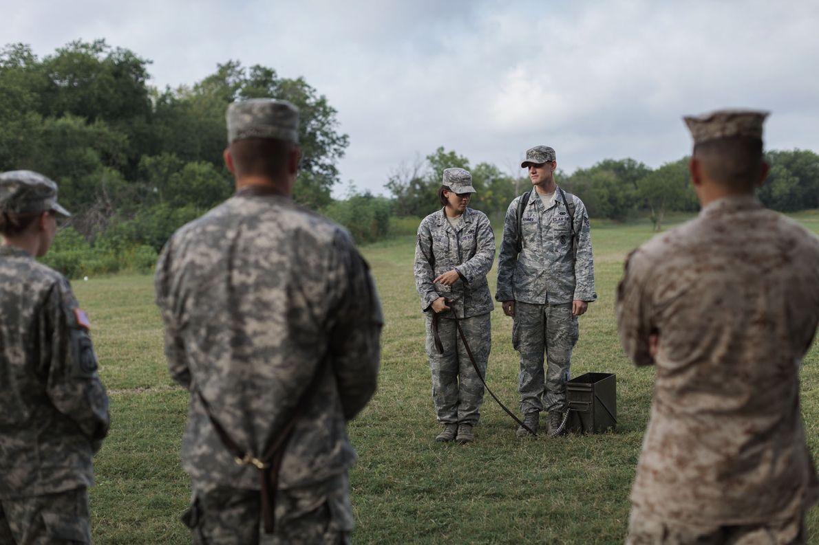 Los estudiantes de la escuela de adiestramiento de perros militares hacen un simulacro con cajas de …