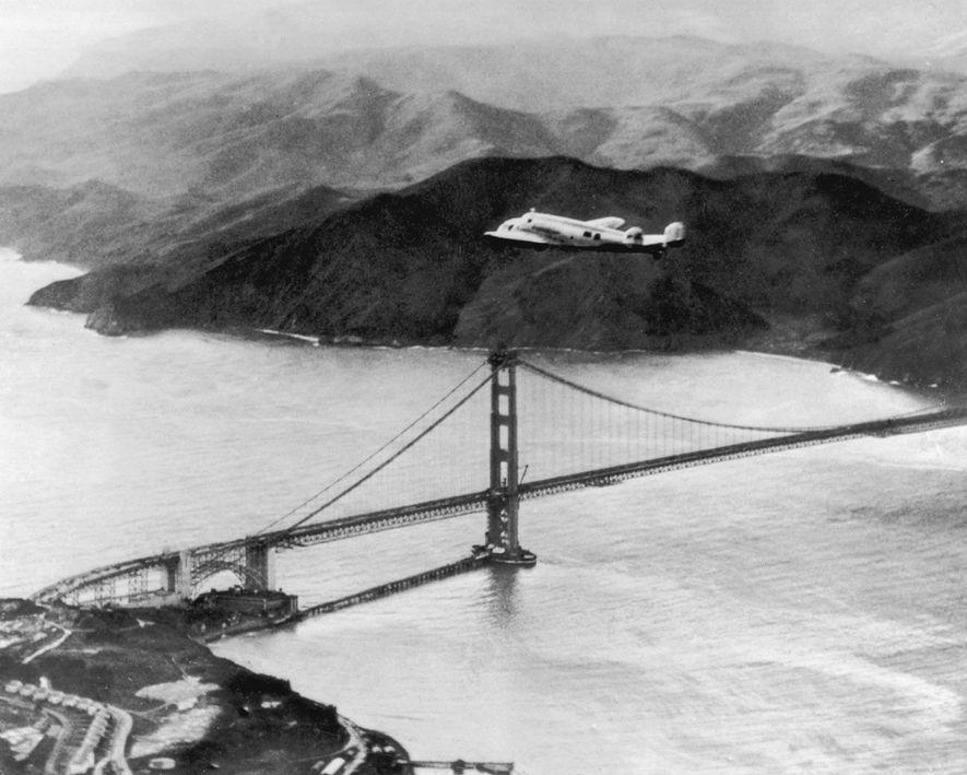 Amelia Earhart y Fred Noonan sobrevuelan el puente Golden Gate al principio de un vuelo para ...