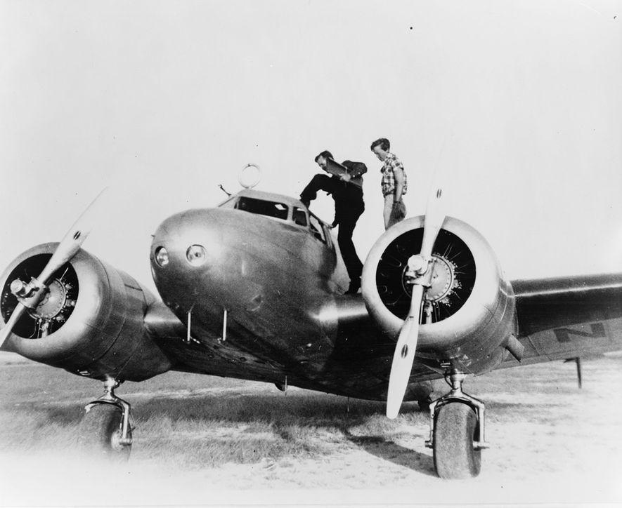 Earhart (a la derecha) y su copiloto Fred Noonan se suben al Electra en una parada ...