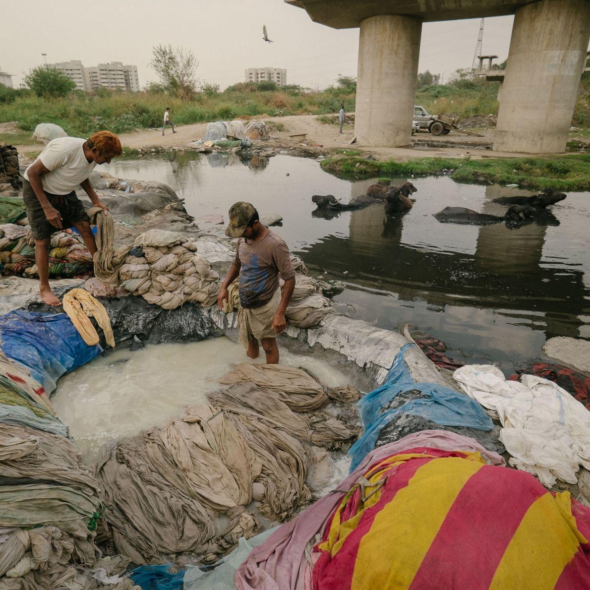 Hombres blanqueando ropa mientras contaminan el rio Yamuna