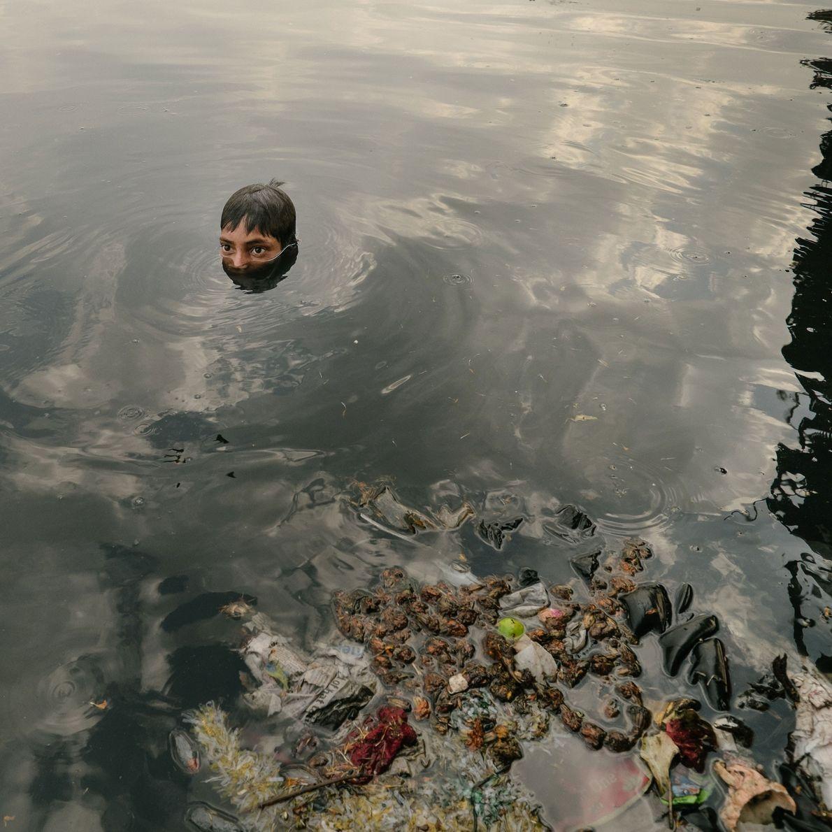 Foto de niños reciclando basura que ha sido arrojada desde el puente