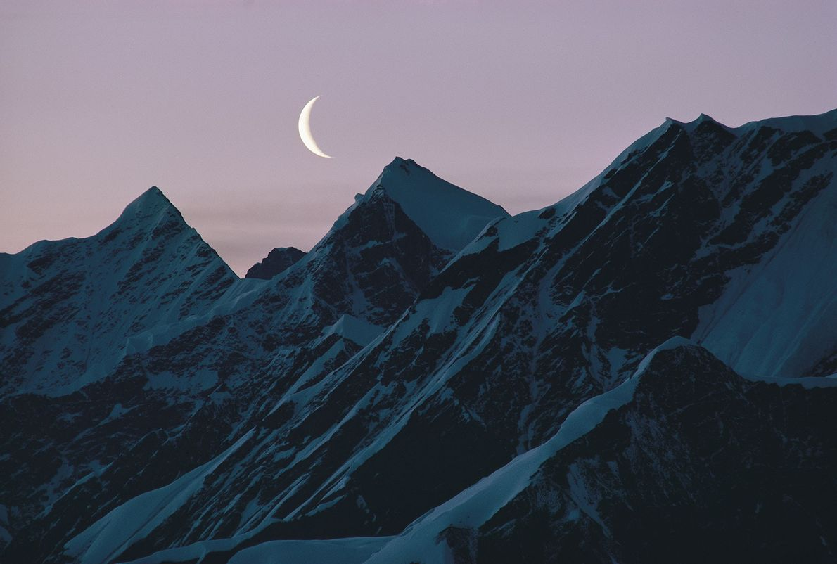 A new moon shines over mountains in Alaska.