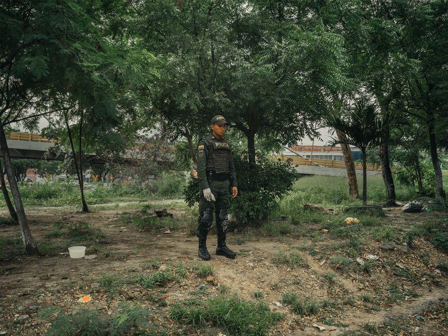 Un policía en un parque junto al canal de Bogotá en Cúcuta, Colombia, un día que ...