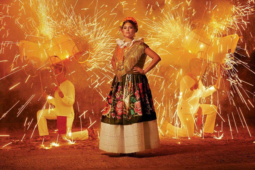 Una mujer lleva un vestido tradicional con flores de seda bordadas en un festival.