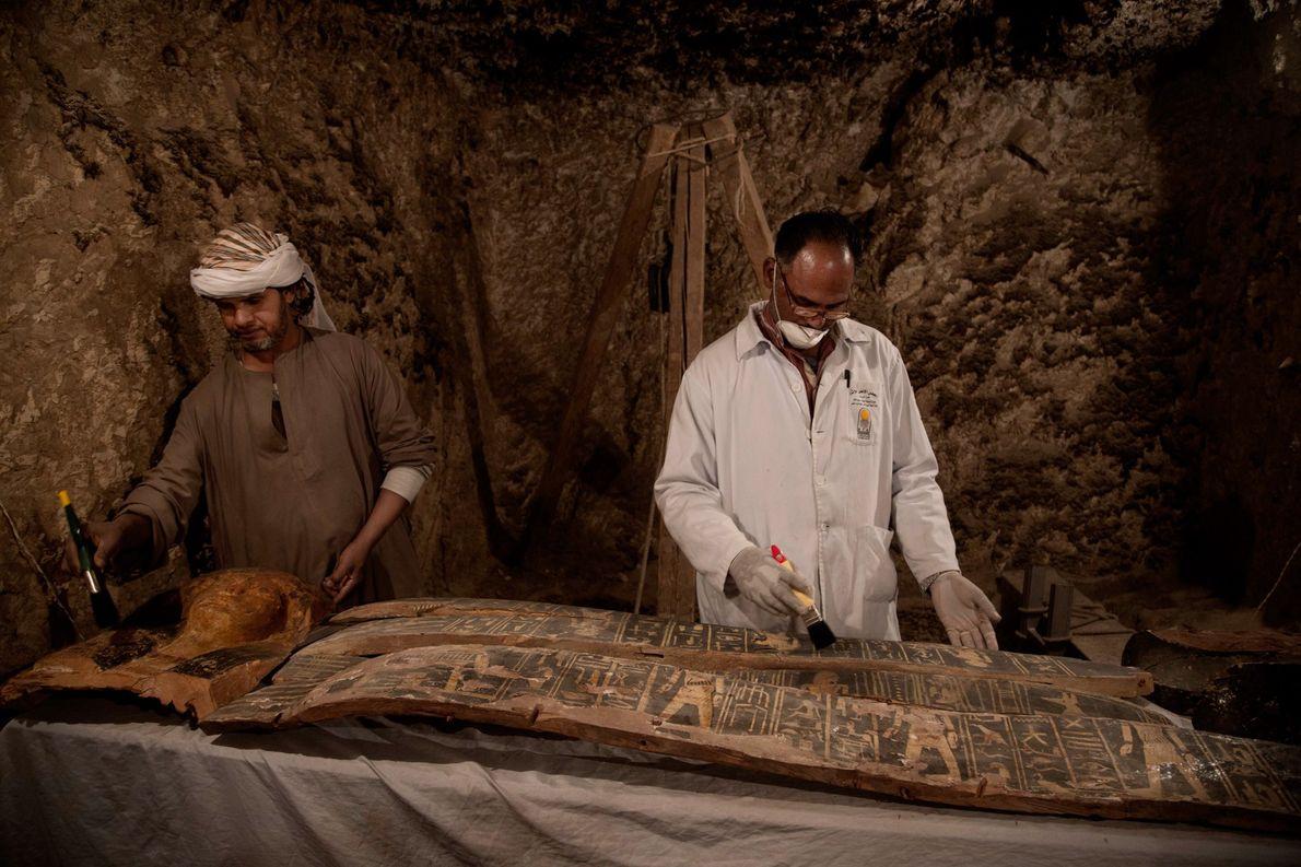 Unos trabajadores egipcios limpian minuciosamente una máscara y un féretro en una tumba recién descubierta llamada …