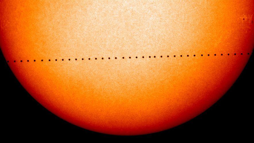Una imagen compuesta muestra el punto negro de Mercurio cruzando el sol, visto desde la Tierra ...