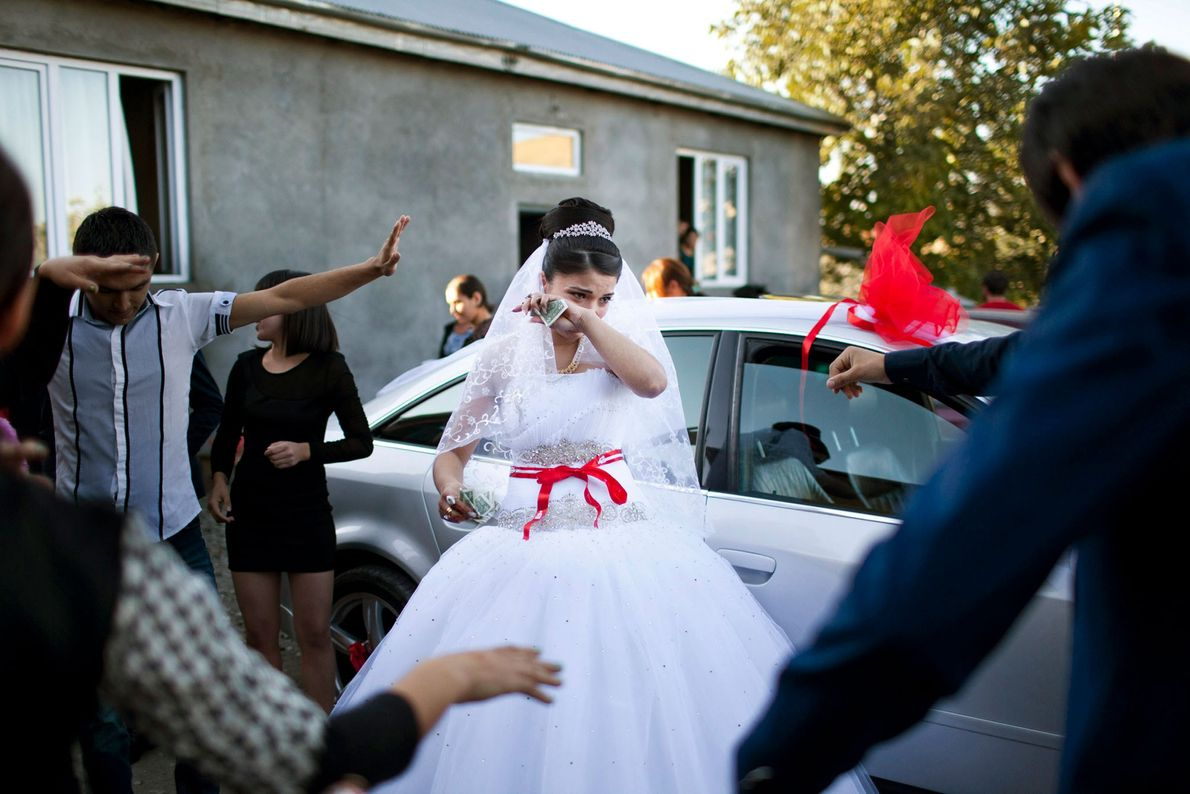 Imagen de una novia llorando mientras su familia baila en torno a ella