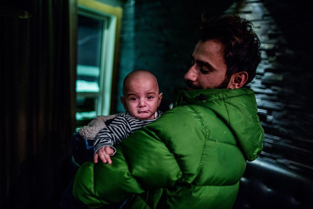 Foto de Mustafa Dagher, de 37 años, sostiene a Nuha, que tiene varicela.
