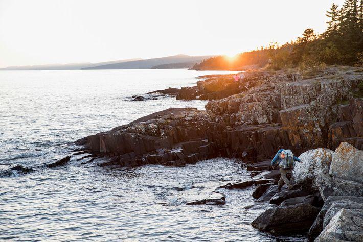 Dupre camina por la costa rocosa del lago Superior.